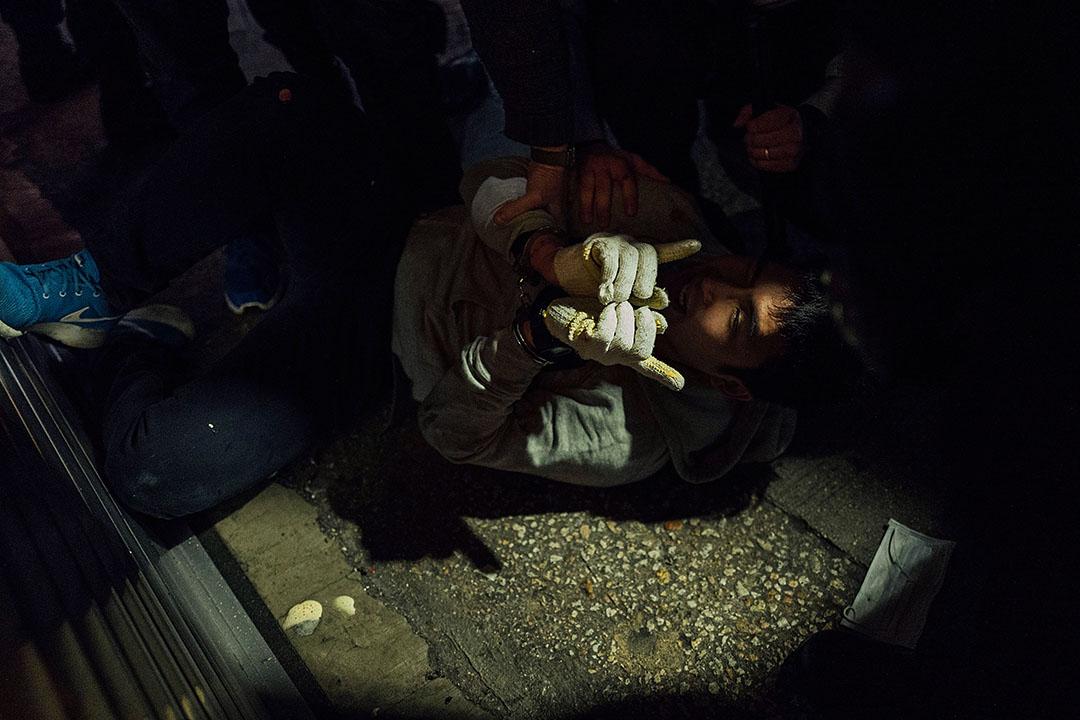 2016年2月9日,旺角,手持盾牌和警棍的防暴警察追截示威者,期間一名示威者被警方按壓地上制服。攝:Anthony Kwan/端傳媒