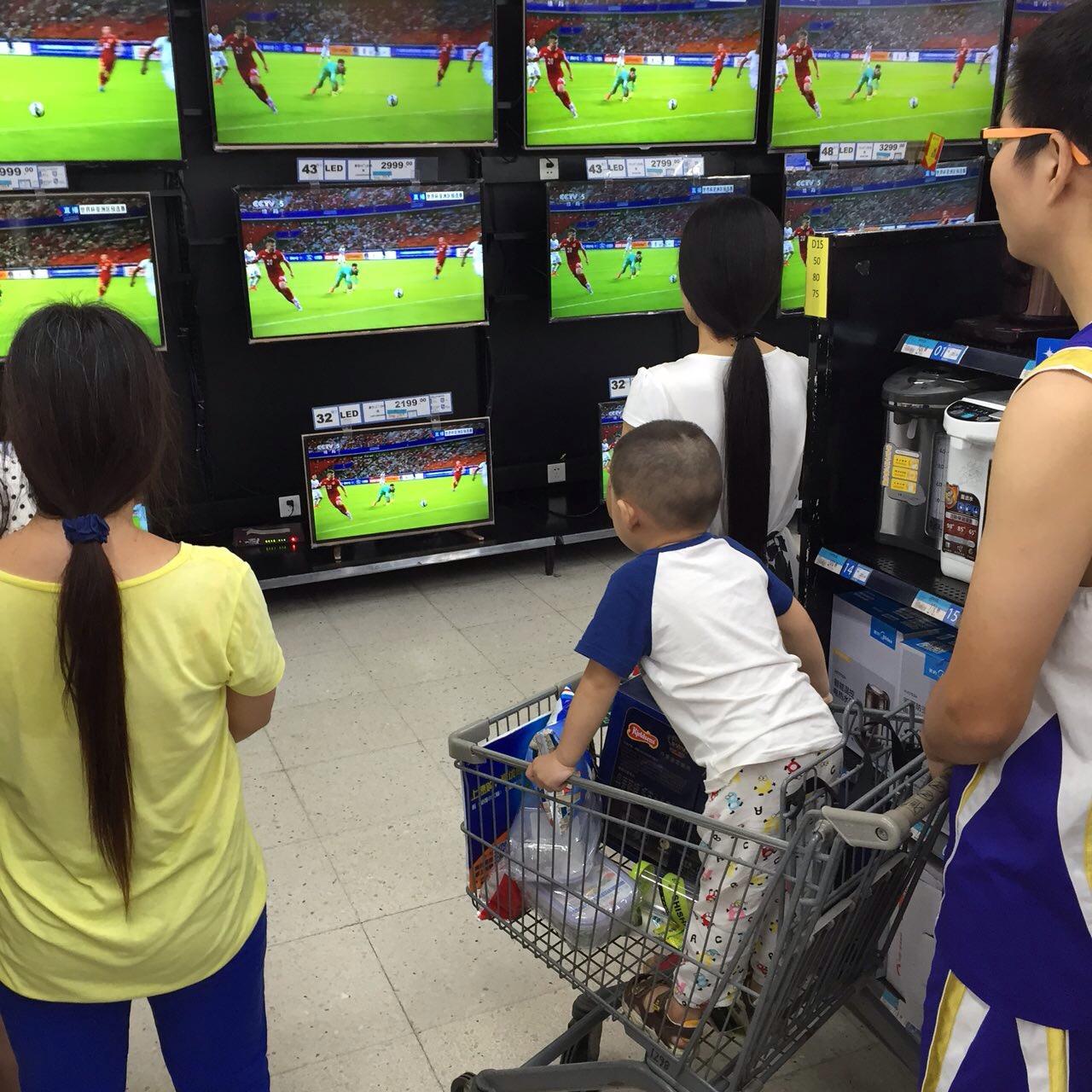 球迷在球場附近的超市觀看賽事直播。