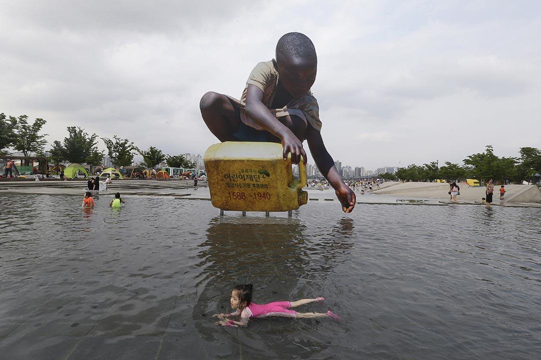 韓國首爾一名女孩在宣傳缺水問題的非洲兒童取水展板前游過。