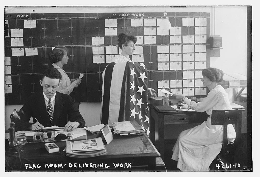 一名女職員披著美國國旗,在美國紐約布魯克林海軍辦公室工作。攝:Bain Collection/Library of Congress/Handout via Reuters
