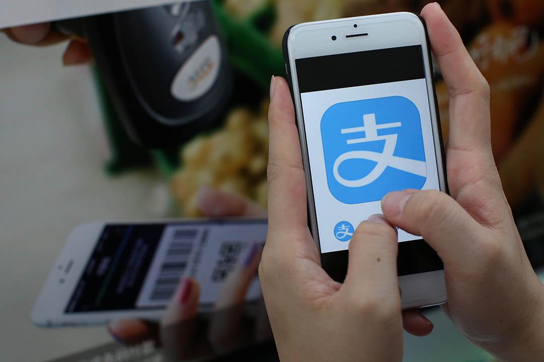 支付寶將登陸台灣,遊客消費時可以直接使用手機裏的支付寶 APP 付款。端傳媒設計圖片
