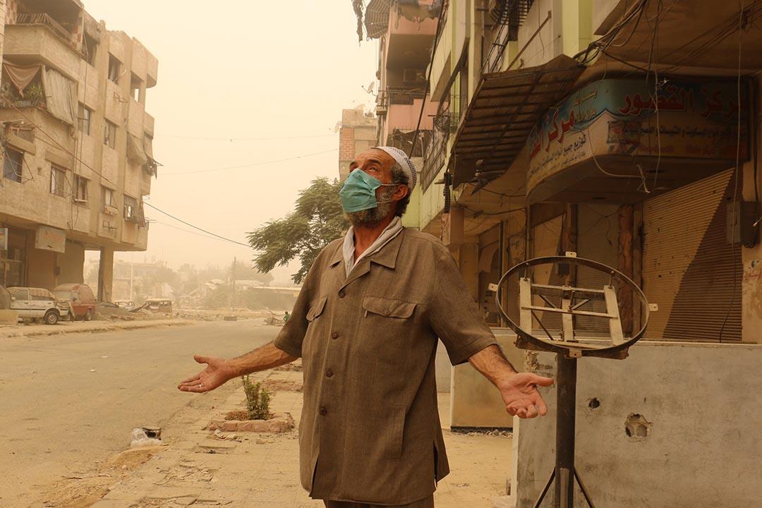 一名敘利亞男子戴著口罩站在大馬士革街頭。攝:Mohammed Khair / Anadolu Agency