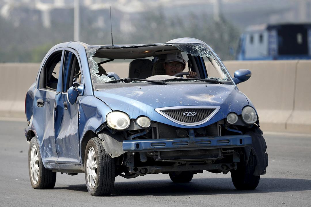 爆炸現場附近,一名男子開著遍體鱗傷的私家車在高速公路上行駛。