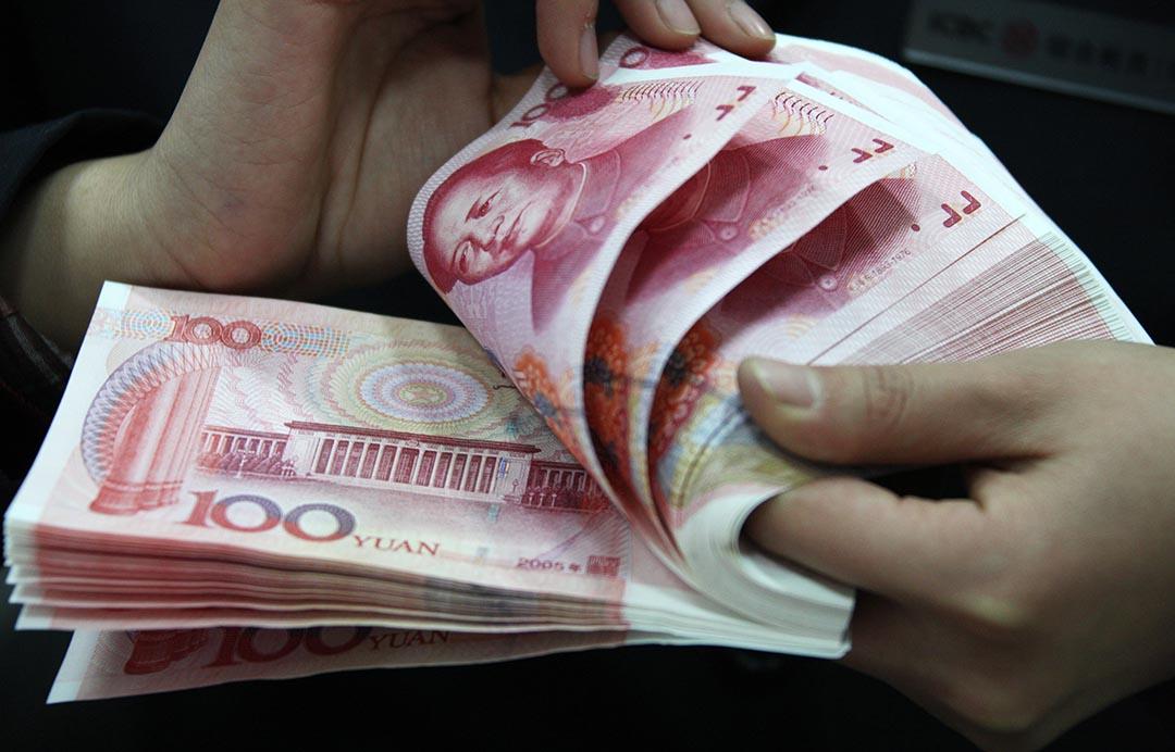 中國大陸民間借貸案司法解釋 9月起施行。圖為一名工作人員在銀行裏點算人民幣。 攝 : Stringer/Getty Images