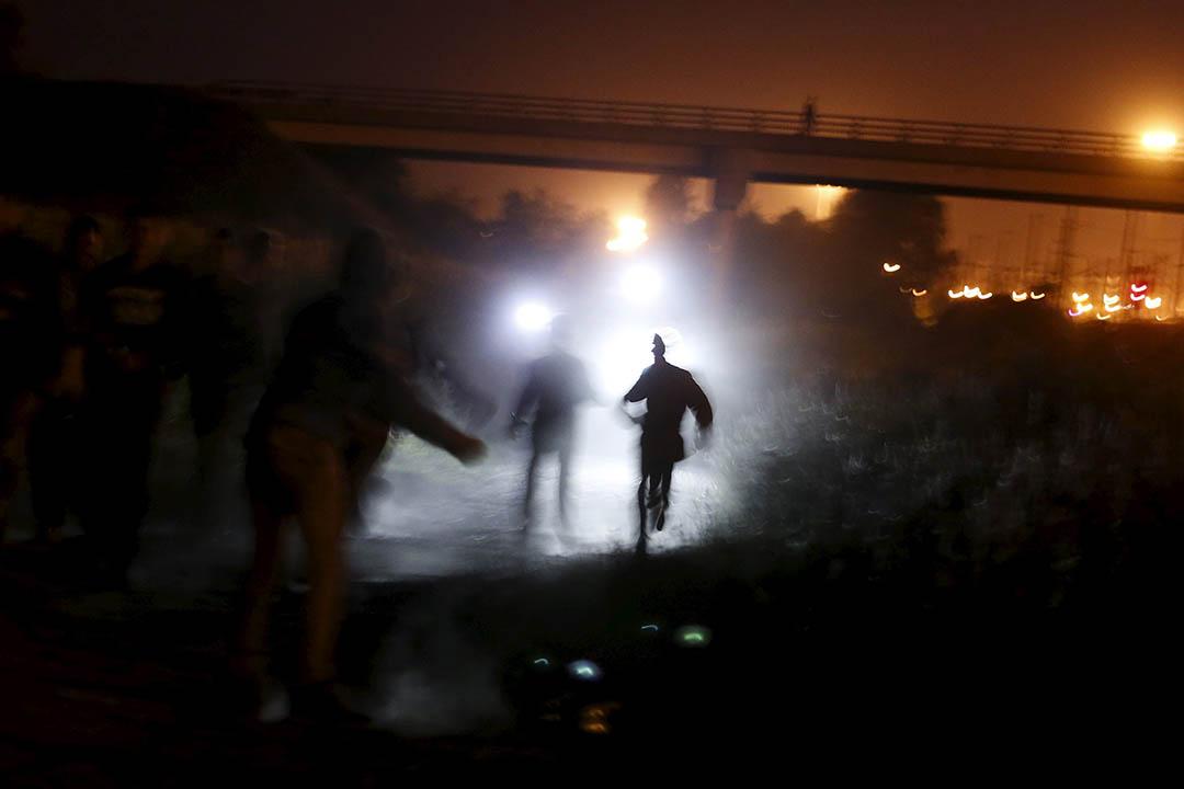 2015年8月5日,法國加來,警察手持電筒追捕企圖通過英法海底隧道偷渡的難民。攝 : Juan Medina /REUTERS