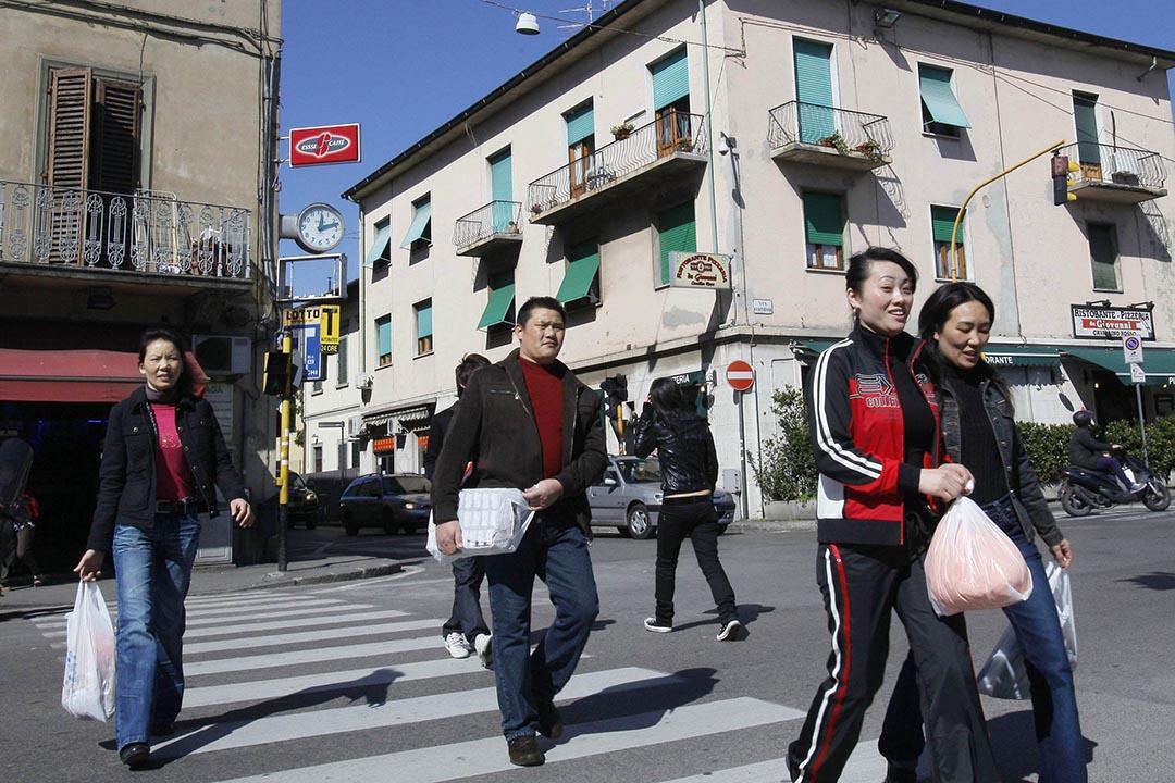 2009年3月13日,意大利的普拉托,幾名中國人經過當地人稱為唐人街的Pistoiese street。攝:FABIO MUZZI /AFP