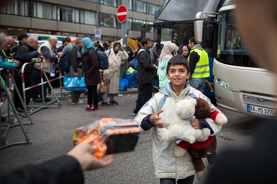 難民等候巴士接載期間,一名小孩收到德國慕尼黑當地人贈送的禮物。 攝:Gordon Wetters/端傳媒