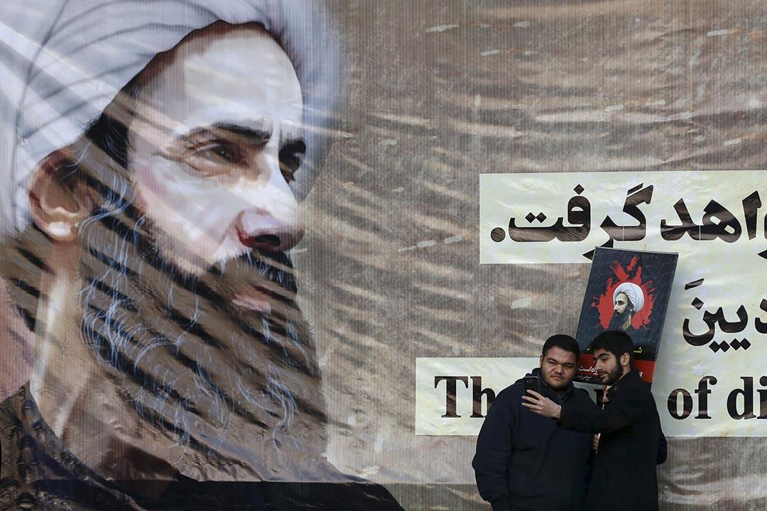 兩名伊朗男子在什葉派教士尼姆爾海報前自拍。攝 : Vahid Salemi/AP