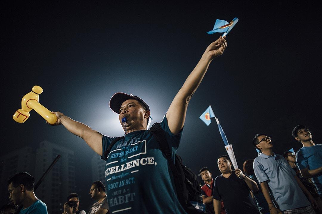 工人黨支持者口吹哨子、手舉「鎚子旗」和打氣棒。攝 : Anthony Kwan/端傳媒