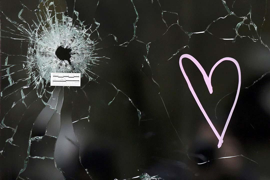 有悼念人士在槍擊現場Le Carillon餐廳的窗戶子彈孔旁畫上心形圖案。攝:Jacky Naegelen/REUTERS