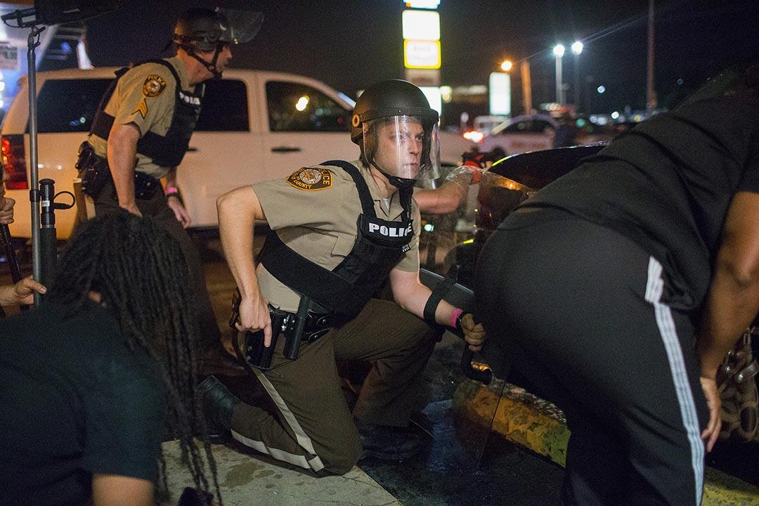 美國密蘇里州弗格森市進行紀念黑人青年布朗(Michael Brown)被槍殺一週年示威活動傳出槍聲,一名警察在掩護中手按槍袋。攝 : Scott Olson/GETTY