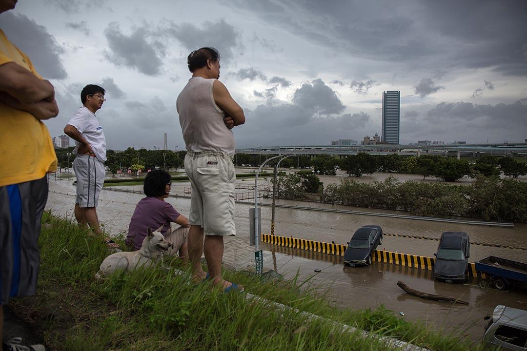 台灣市民在堤上觀看被淹沒的低窪地區。攝 : Billy H.C. Kwok/端傳媒