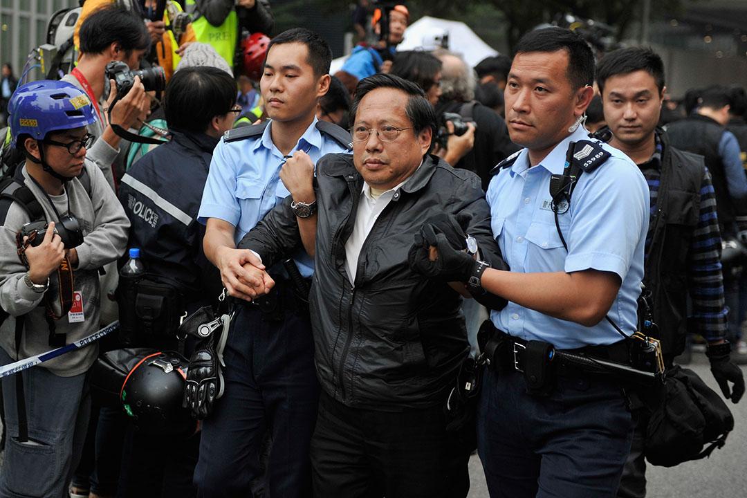 2015年12月11日,金鐘佔領區被清場,留守的立法會議員何俊仁被警員帶走。攝:Lucas Schifres/GETTY