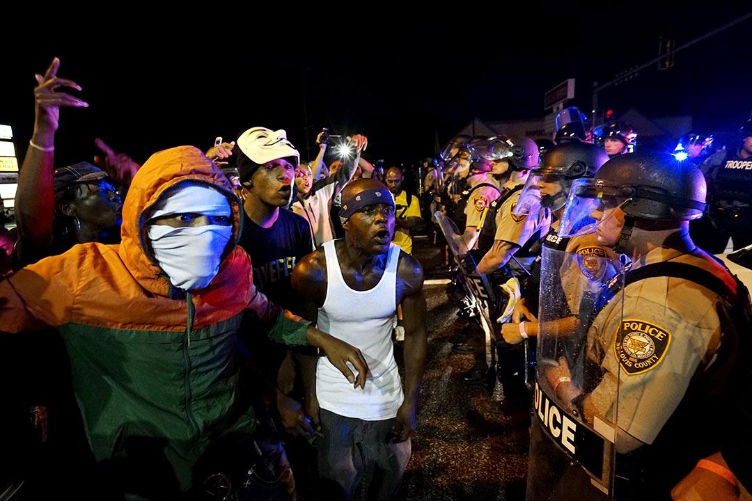 美國密蘇里州弗格森市進行紀念黑人青年布朗(Michael Brown)被槍殺一週年活動,示威者向在場警察呼喊。攝 : Rick Wilking/REUTERS