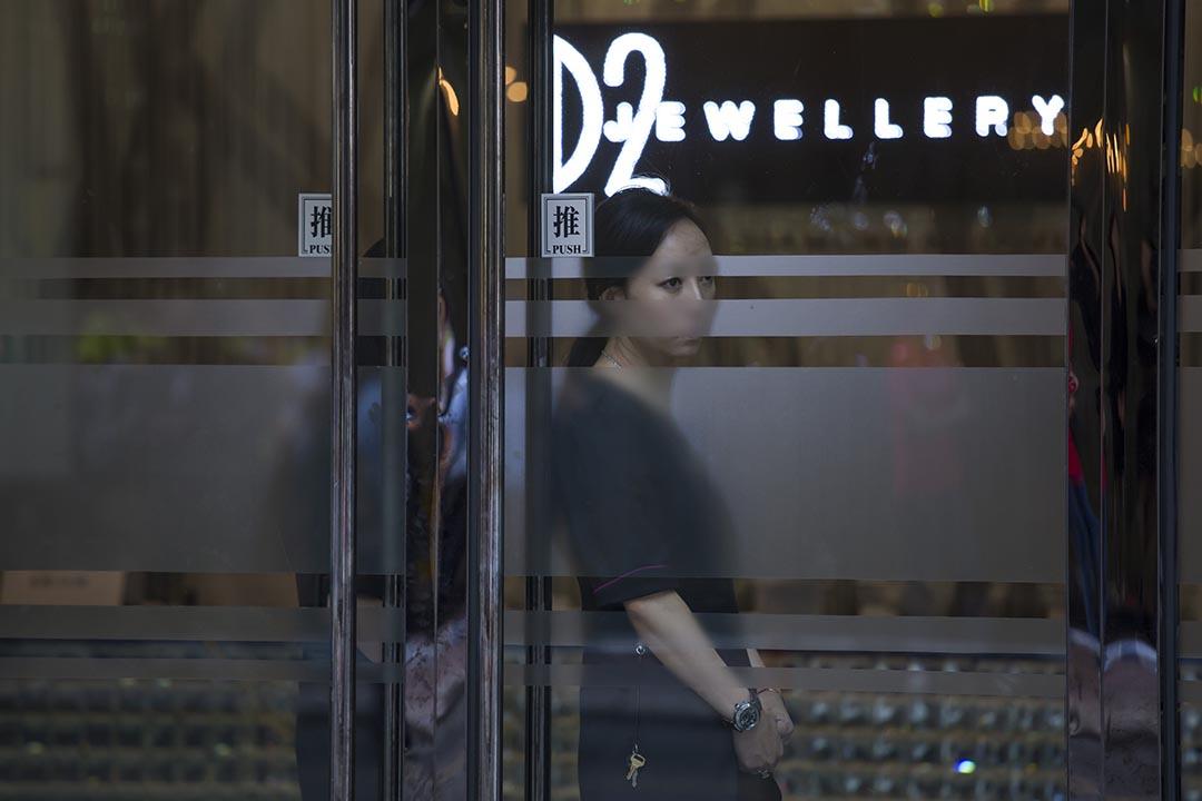 D2 Jewellery職員在店門口往外看。攝:羅國輝/端傳媒