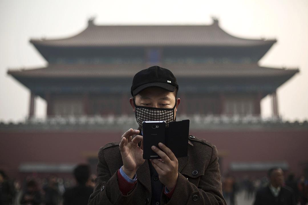 2016年11月20日,中國北京,一名男子在紫禁城外戴着口罩使用智能電話。攝:Kevin Frayer/GETTY