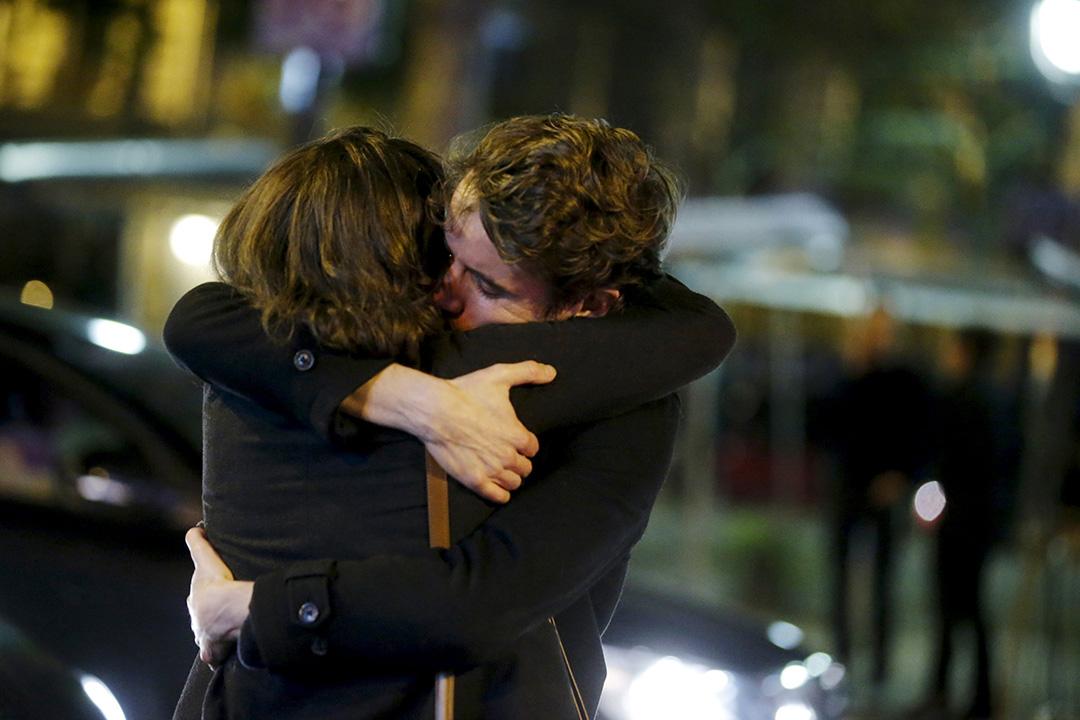 2015年11月14日,巴黎,巴塔客蘭音樂廳發生恐襲後,一對男女在音樂廳外的街道上相擁。攝:Christian Hartmann/REUTERS