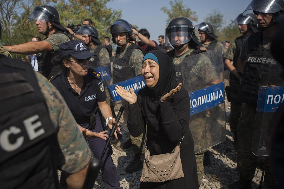 希臘邊境城市Idomeni大批難民和警方衝突,一名敘利亞難民婦女和女兒失散後在警察中痛哭。