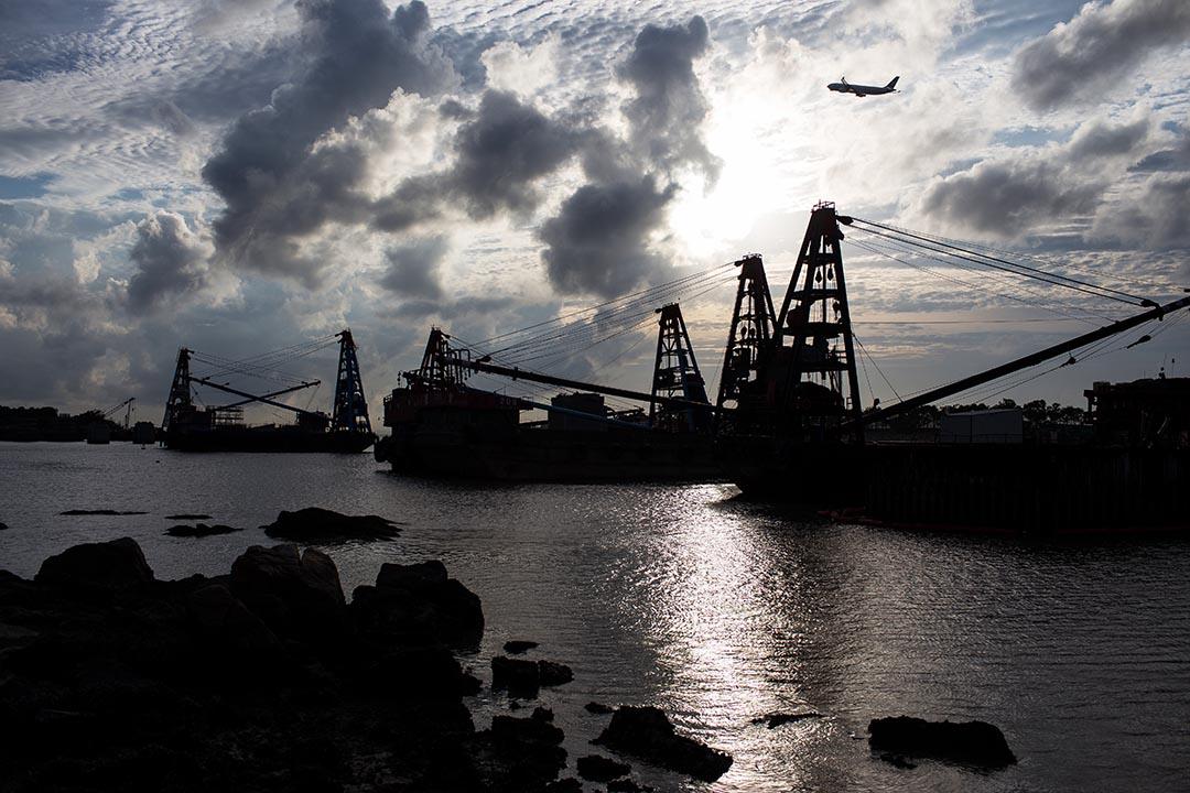 飛機在港珠澳大橋施工地盤上飛過。東涌沙螺灣鄰近赤臘角機場,港珠澳大橋香港段正在施工,工程日以繼夜在進行。攝 : Billy H.C. Kwok/端傳媒