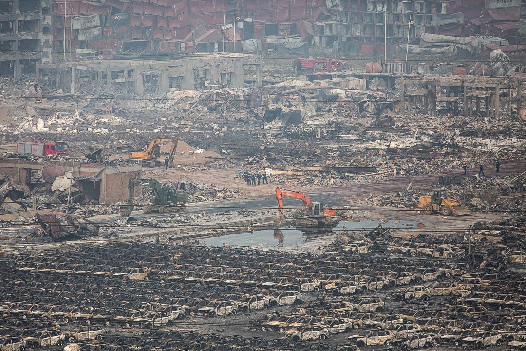 帶著面罩的工作人員在爆炸現場走過。攝: Billy H.C. Kwok/ 端傳媒