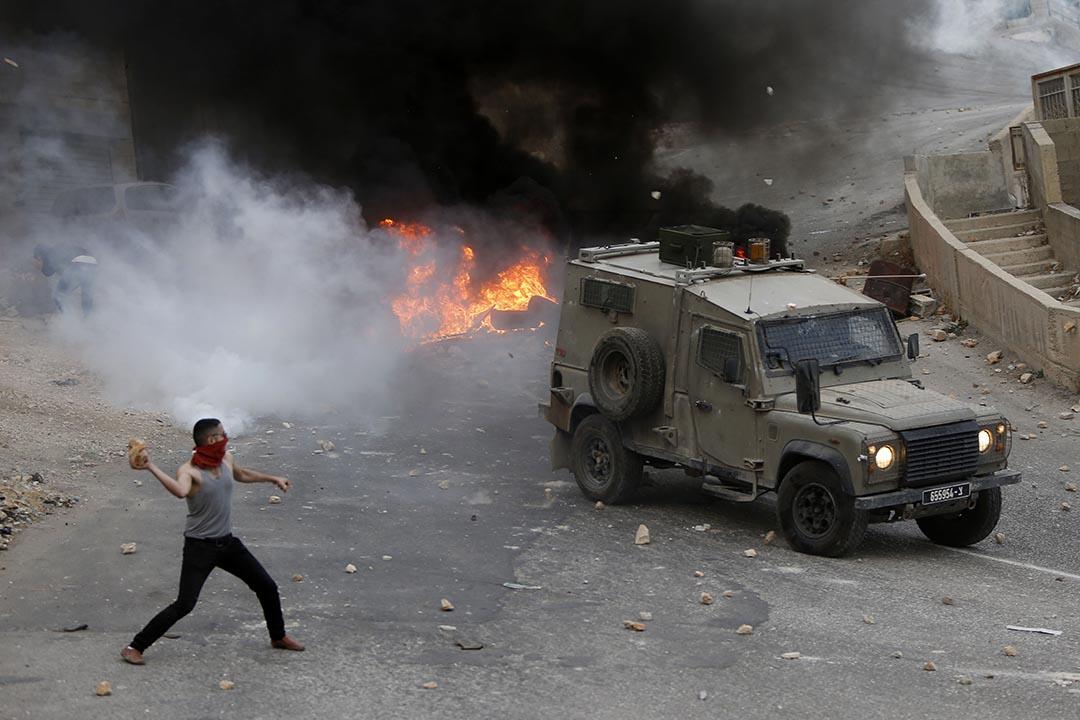 2015年10月6日,約旦河西岸,巴勒斯坦青年向以色列軍車投擲石頭。攝:Majdi Mohammed/AP