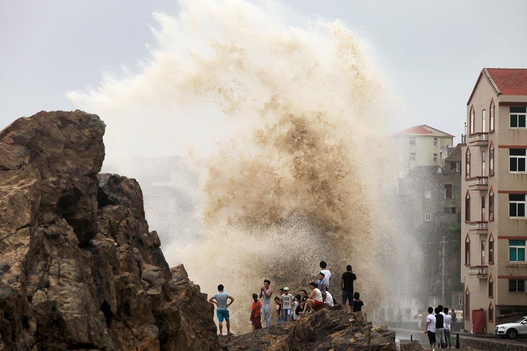 在中國浙江台州,市民在岸邊觀看海浪拍打防波石。攝 : Stringer/REUTERS