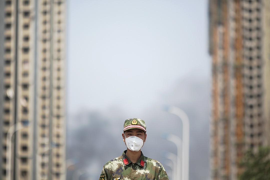 一名在天津的官兵戴上口罩指揮交通。 攝 : Damir Sagolj/REUTERS