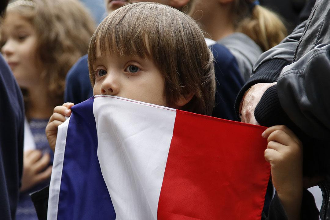 2015年11月14日,哥倫比亞,巴黎恐襲後世界各地有不同悼念儀式。圖中的男孩手持法國國旗參與在哥倫比亞首都舉行的追悼會。攝:Fernando Vergara/AP