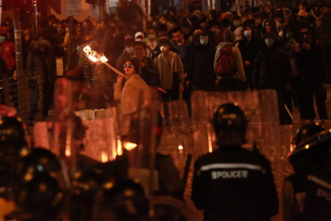 凌晨約5時,有示威者用竹枝造成火把投向警察。攝:Billy.H.C.Kowk/端傳媒