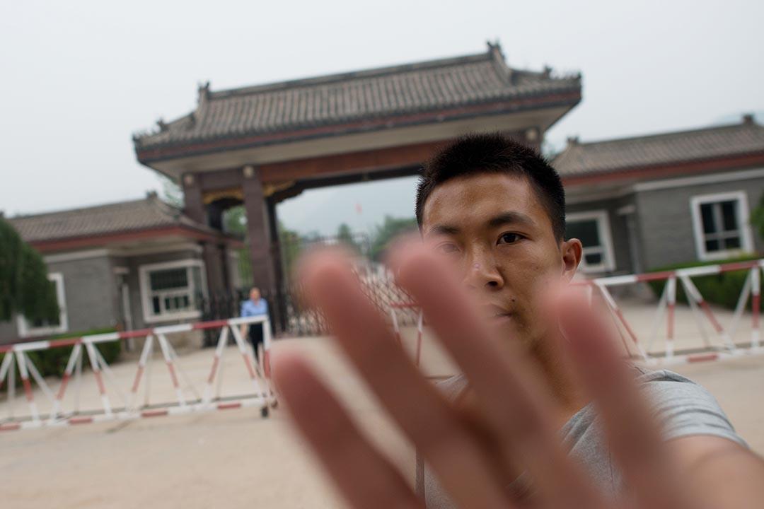 便衣警察阻止記者拍攝北京秦城監獄外的環境 。攝:Ed Jones/ AFP。