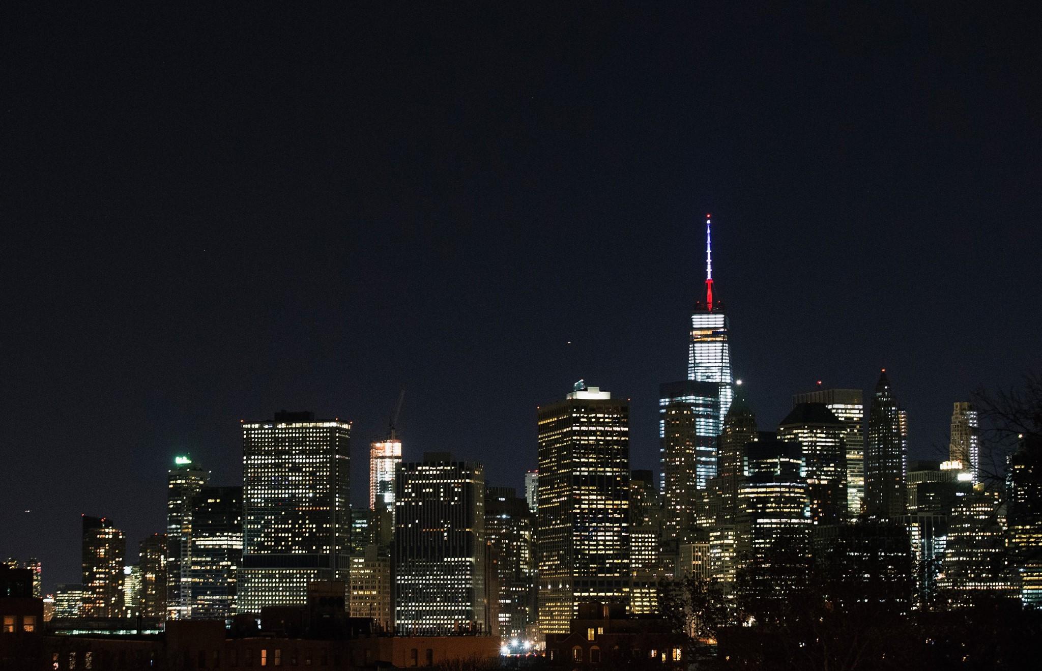 美國紐約世貿大樓,在夜空中打出藍白紅三色的法國國旗燈色,悼念恐襲事件中的死難者。攝:Daniel Pierce Wright/Getty Images