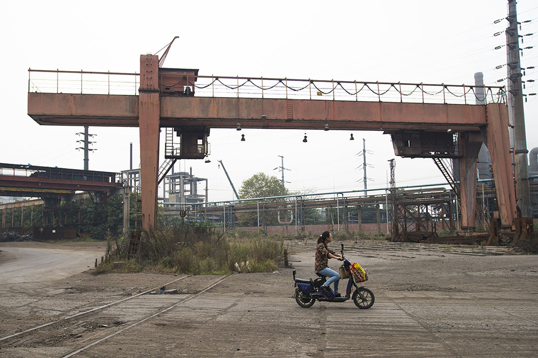 攀成鋼老廠區裏只剩下一個車間還在開工,10月19日下午,下班的工人騎着摩托車回家。攝: Yue Wu/端傳媒