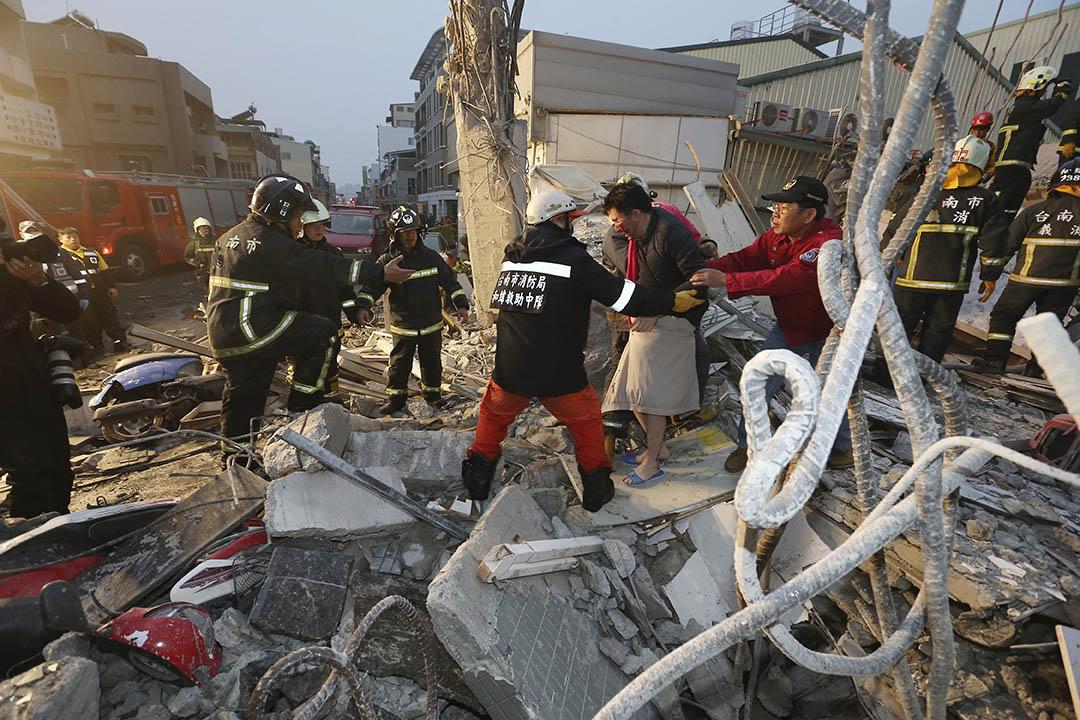 2016年2月6日,台南,救援人員協助一名傷者離開已倒塌的樓房。攝:AP Photo