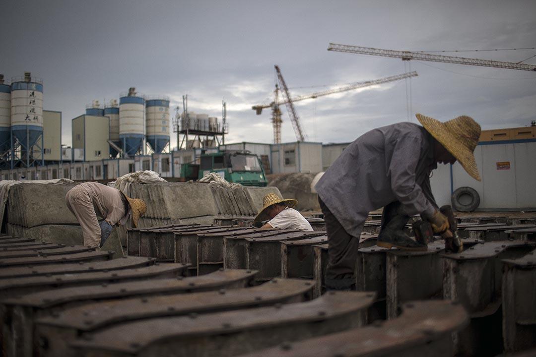 人工島上,工人帶著草帽裝嵌大橋部件,不分男女,日夜趕工。