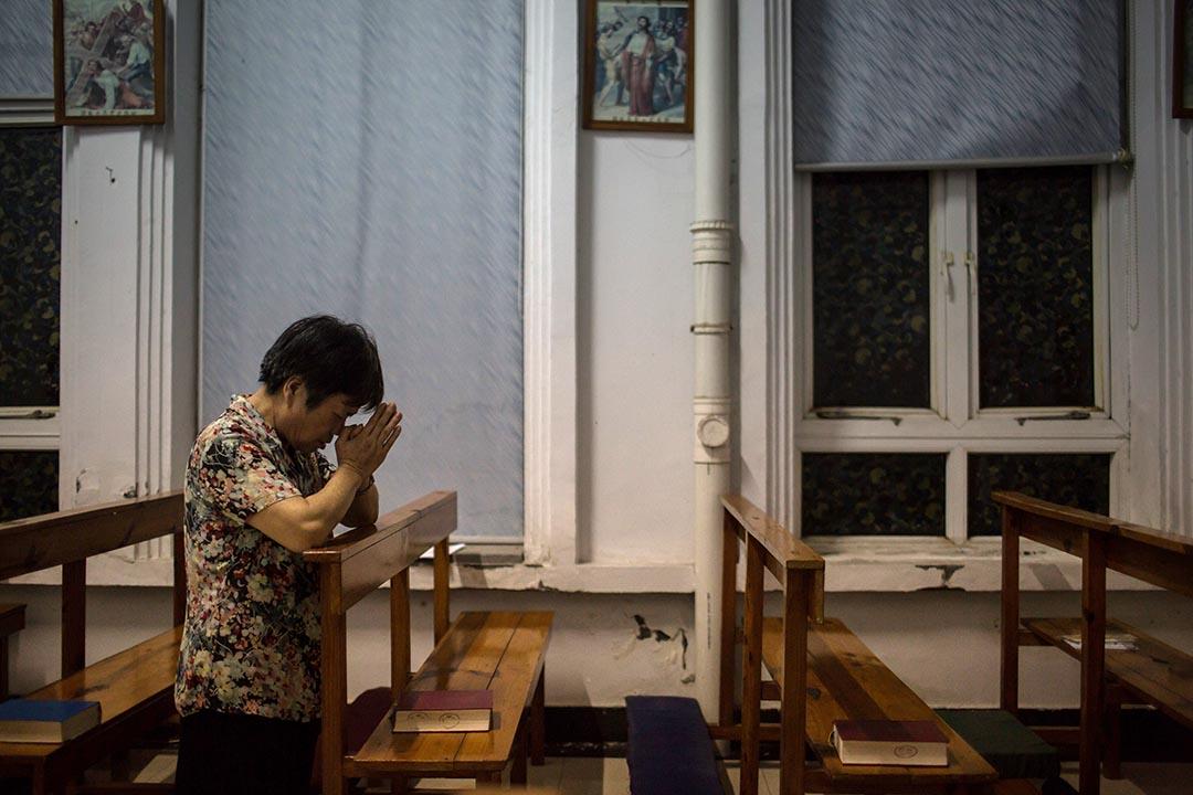 一名教徒在杭州蕭山天主堂祈禱。攝 : Billy H.C. Kwok/端傳媒