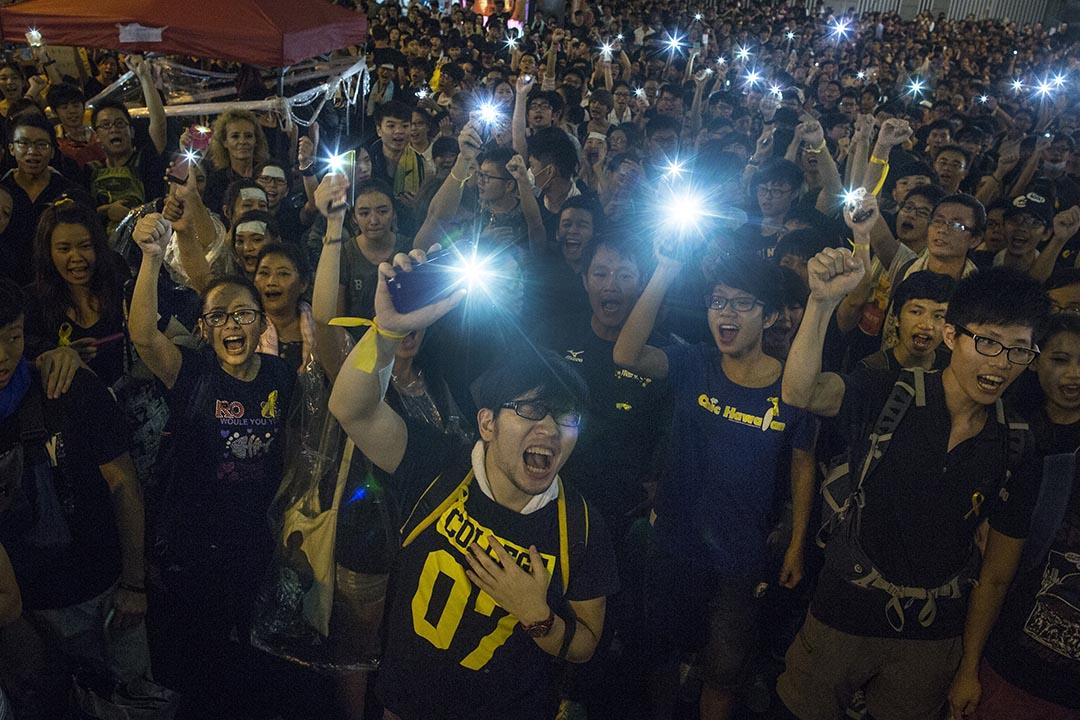 2014年9月30日,參與佔領運動的學生示威者亮起燈光,叫喊口號。 攝: Paula Bronstein/Getty Images