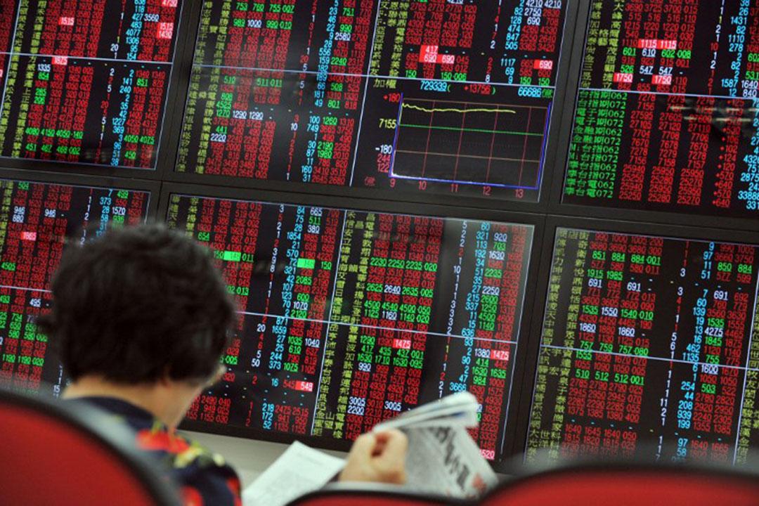 圖為台灣一家證券交易所,一名女士正在閱讀財經新聞。攝:Mandy Cheng/AFP