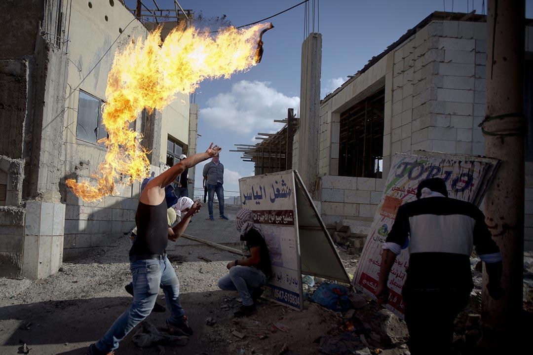 2015年10月6日,約旦河西岸城市拉姆安拉,巴勒斯坦男子向以色列軍人投擲燃燒彈。 攝:Majdi Mohammed/AP