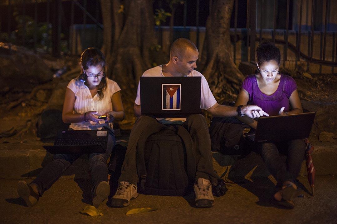古巴青年使用 WiFi 熱點在行人道旁上網。攝 : Samuel Corum / Anadolu Agency