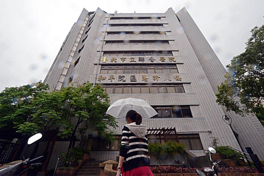 一名女子在台北市一間公立醫院前走過。攝:Sam Yeh/AFP