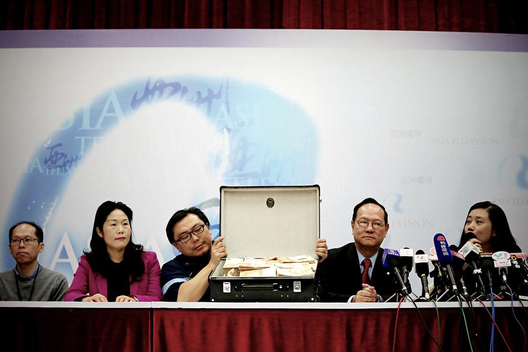 2016年3月4日,亞視投資者一方中午在亞視大埔廠房召開記者會,期間展示一箱500萬元現金及一張500萬元支票。右一為亞視投資者司榮彬的代表何子慧。攝:盧翊銘 / 端傳媒