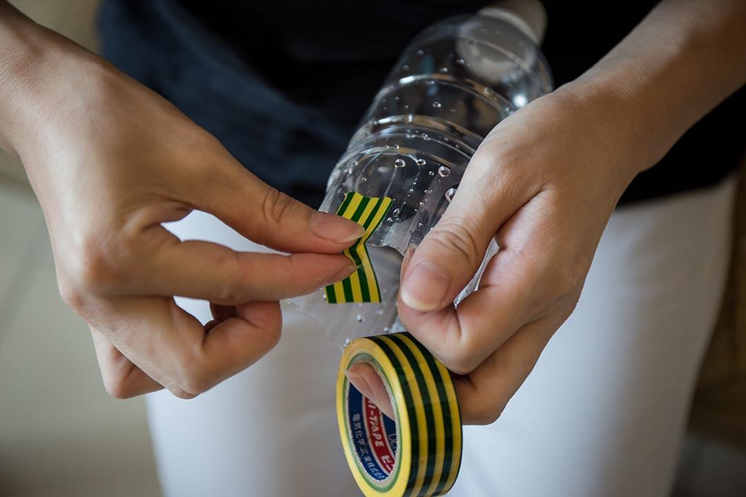 2. 剪開膠樽底部,在樽邊平均貼上三塊電線膠布,再在每塊膠布上打孔。