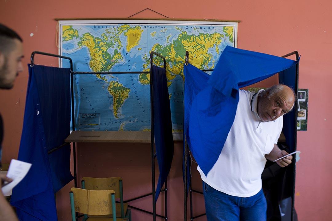 希臘就業是否接受債權人方案舉行公投,一名男子在投票後準備離開。攝:Emilio Morenatti/AP