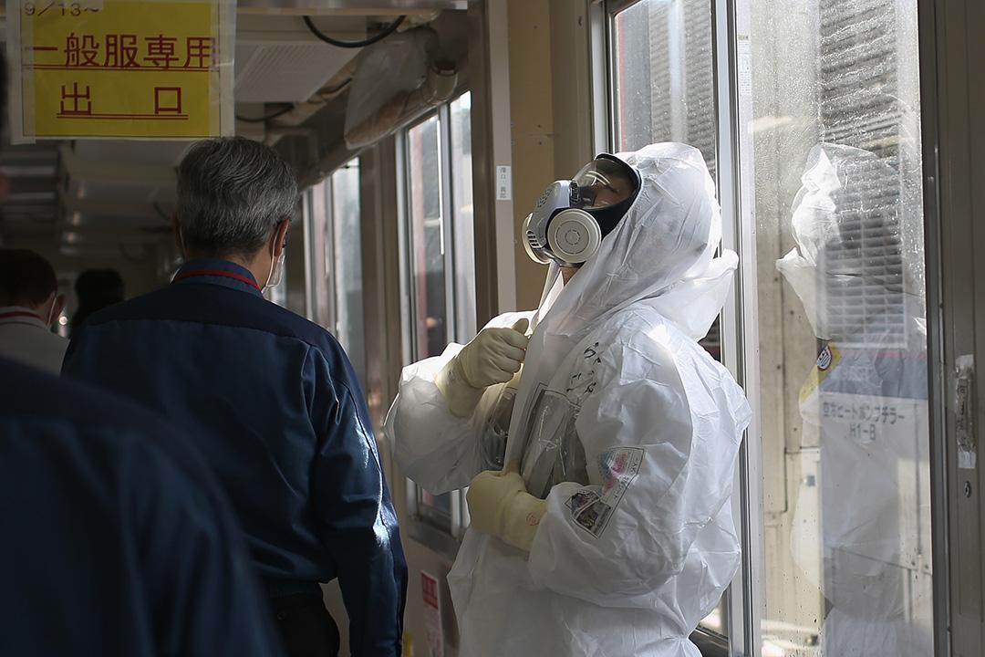 工作人員在進入核污染區前,在一座抗震建築內換上保護衣物。攝:Christopher Furlong/GETTY