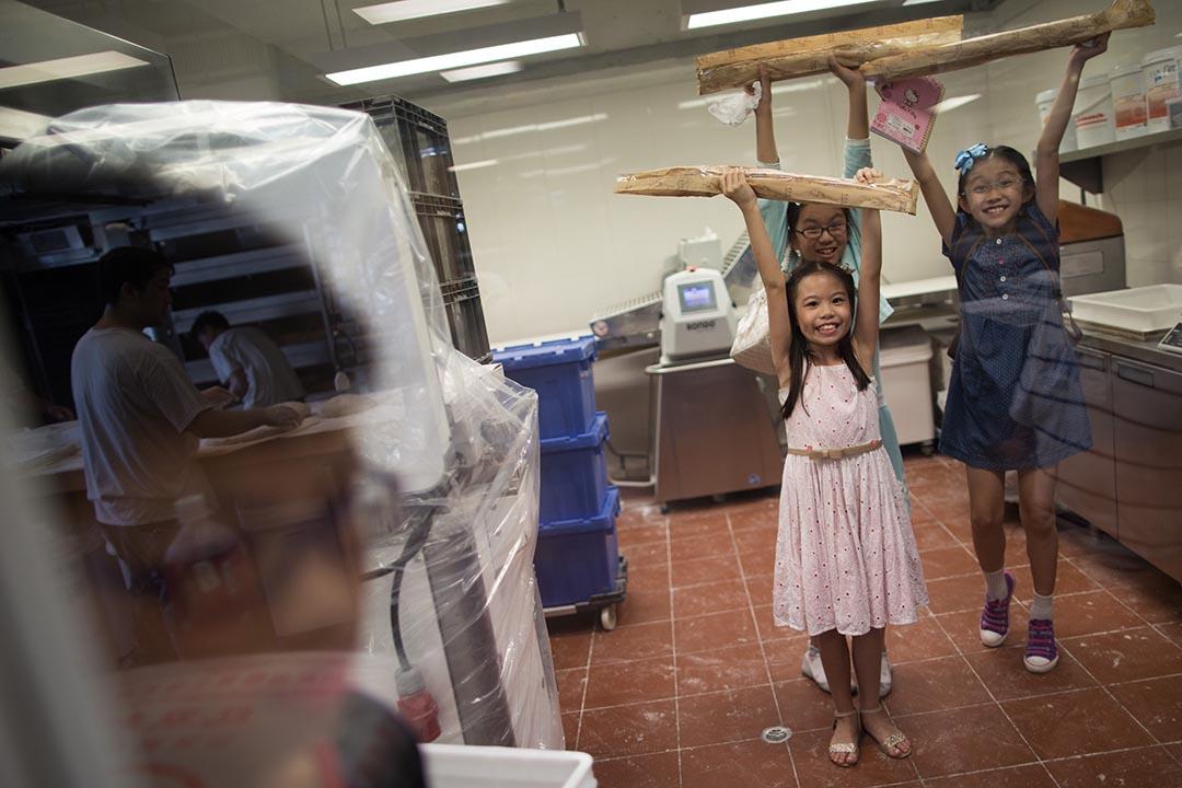 小女生躲進工場後面有冷氣的地方,拿著戰利品雀躍地起舞。