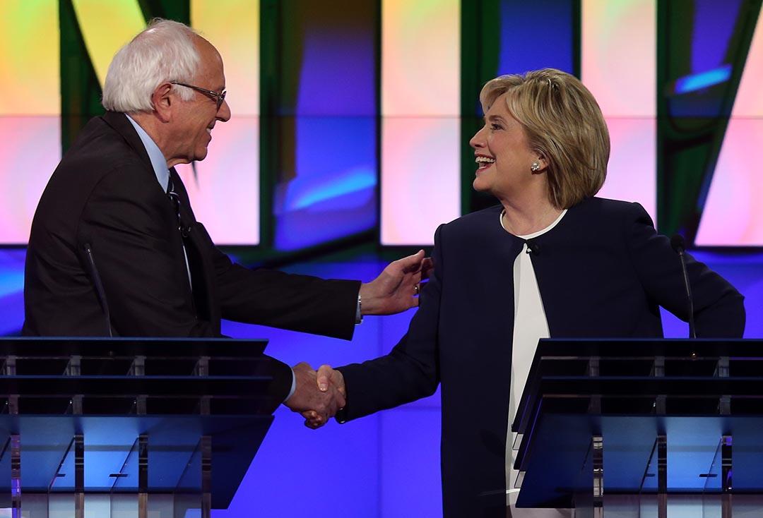 美國民主黨總統參選人伯尼·桑德斯(左)和希拉莉·克林頓在辯論現場握手。攝 :  Joe Raedle/GETTY