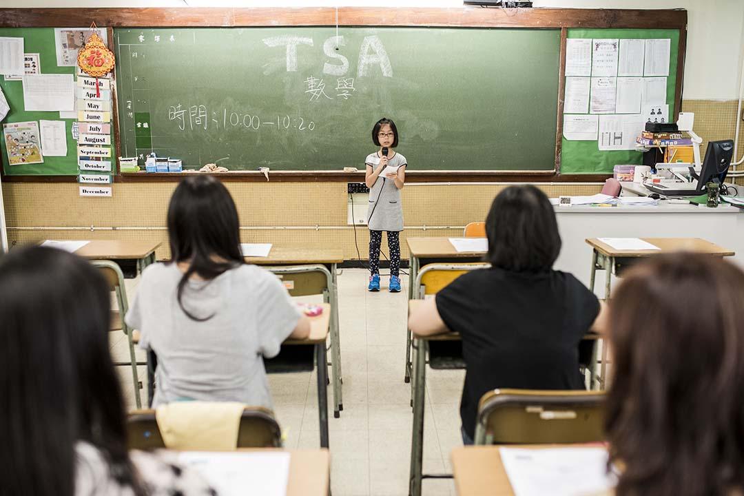 家長參與《端傳媒》組織的模擬 TSA 考試,設身處地嘗一嘗孩子的感受,整個過程由小朋友「監考」。攝:Xaume Olleros/端傳媒