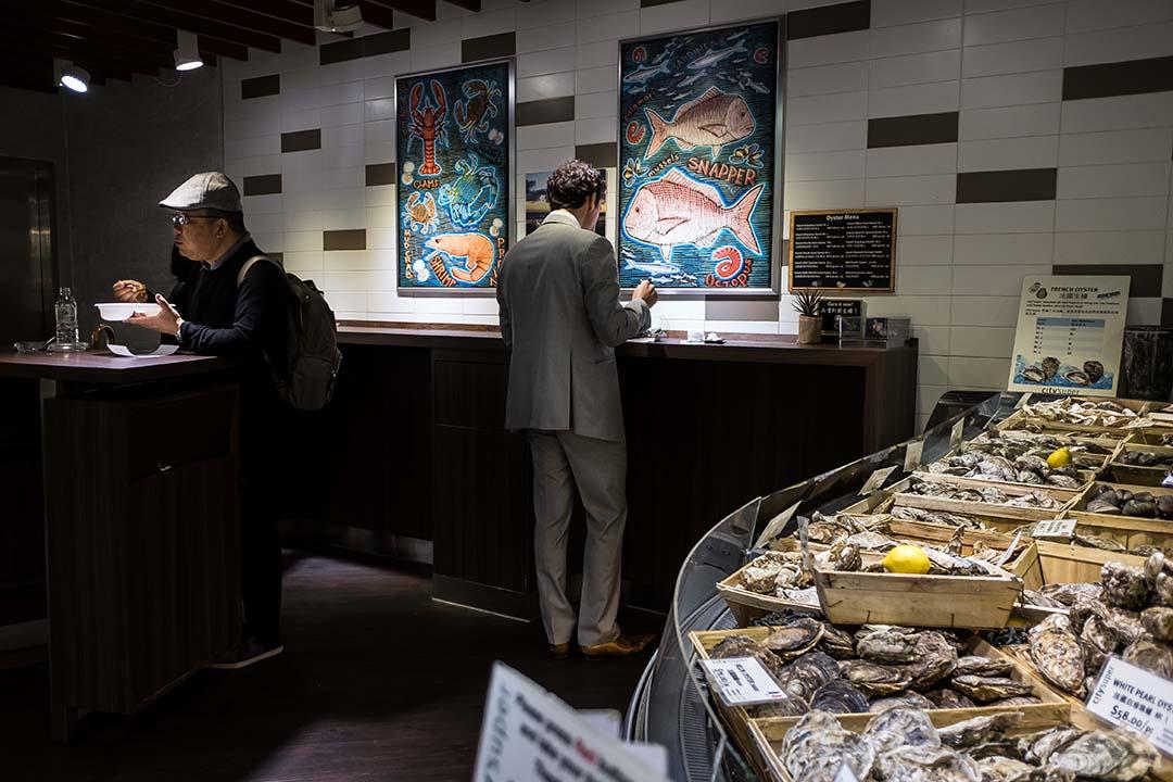 顧客在超市內品嚐來自世界各地的海鮮,當中包括日本福岡海域的生蠔。攝:Billy H.C. Kwok/端傳媒