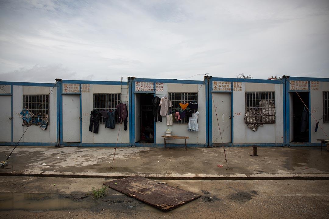人工島的臨時宿舍由貨櫃一排排並列組裝而成,工人與其家眷起居生活均在島上,不時有小孩在宿舍外追逐,像個自成一角的島上社區。
