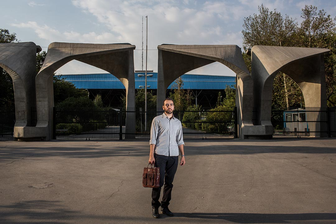 Mohammad Ali Mir Bagheri,三十歲的德黑蘭大學哲學系博士生,站於大學入口處。德黑蘭大學是伊朗其中一間「常春藤盟校」。為了維持生計,他正在做多份兼職。但他無法找到與他學科有關的工作。攝:Arash Khamooshi/端傳媒